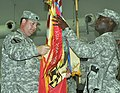 US Army 52515 Col. Larry Phelps, 15th Sustainment Brigade commander, and Command Sgt. Maj. Nathaniel Bartee, 15th SB senior noncommissioned officer, uncase their unit's guidon in the Morale, Welfare and Recreation.jpg