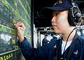 US Navy 030830-N-8955H-009 Operations Specialist 3rd Class Ji Young An, from Frederick, Md., updates the bridge surface contact status board.jpg