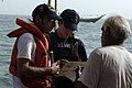 US Navy 050613-N-4309A-126 Sailors assigned to the coastal patrol boat USS Chinook (PC 9), with the assistance of an Arabic translator ask questions of a local fisherman.jpg