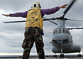 US Navy 070612-N-5067K-085 Aviation Boatswain's Mate Airman Lowel A. Shorey III, a landing signalman enlisted (LSE), signals a Marine CH-46 Sea Knight during take off aboard amphibious transport dock USS Juneau (LPD 10).jpg