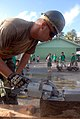 US Navy 070830-N-4267W-010 Schoolchildren watch as Builder 2nd Class Mike Carman, with Naval Mobile Construction Battalion (NMCB) 7, uses a circular saw to cut out posts to be used as a frame for a new playground at Rairok Elem.jpg