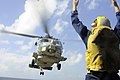 US Navy 100105-N-1291E-056 Boatswains Mate 3rd Class Nicholas Valle directs an SH-60 Seahawk helicopter assigned to Helicopter Anti-Submarine Squadron Light (HSL-37) during a vertical replenishment aboard the guided-missile cru.jpg