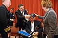 US Navy 100115-N-6651N-011 The wife and son of World War II veteran Seaman 1st Class Arthur Bialik put a Navy Region Southeast ball cap on his head after a formal presentation of medals presented by Capt. Matthew Straughan.jpg