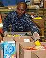 US Navy 100626-N-9634R-015 Aviation Support Equipment Technician 1st Class Nigel Noel separates damaged food products from donated items during a community service project with the Feed Nova Scotia food bank.jpg