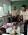 US Navy 100811-N-2389S-063 Culinary Specialist 2nd Class John Davis gives a Navy ball cap to a patient in the children's hospital as part of Caps for Kids during Chicago Navy Week.jpg