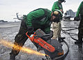 US Navy 100922-N-7103C-091 Aviation Boatswain's Mate 3rd Class Max Torres, from Houston, uses a chop saw to cut through a worn arresting cable in p.jpg