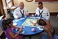 US Navy 110713-N-NT881-124 Personnel Specialist 2nd Class James Vail, left, and Boatswain's Mate 2nd Class Nathaniel Eaton play board games with ch.jpg