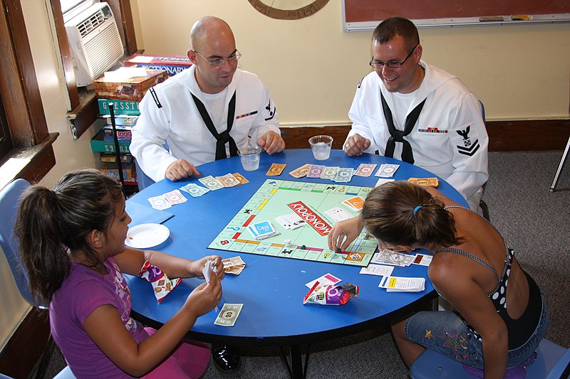 US Navy 110713-N-NT881-124 Personnel Specialist 2nd Class James Vail, left, and Boatswain%27s Mate 2nd Class Nathaniel Eaton play board games with ch.jpg