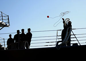 US Navy 120109-N-YM863-080 A Sailor aboard The Arleigh Burke-class guided-missile destroyer USS Spruance (DDG 111) tosses out a heaving line as th.jpg