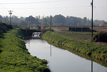 A stream perhaps 20 feet (6 m) wide flows between grassy banks and telephone poles on either side. Waterfowl float on the stream near a low bridge in the middle distance. In the far distance is a line of trees.