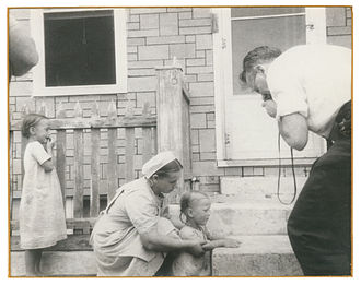 Victor A. McKusick - Victor McKusick taking a picture of an Amish child's hands during his study of the Amish.