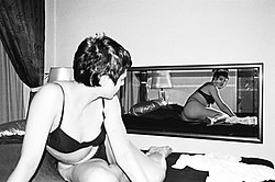 Woman lying on bed, looking at mirror, Berlin 2001.jpg