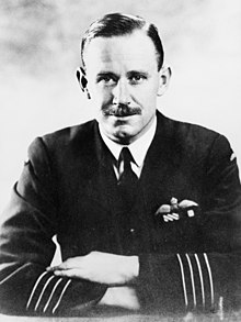 Half-length portrait of moustachioed man in military uniform, with aviator's wings on left breast pocket and four stripes on jacket forearms