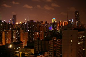 A cityscape with block-like, shadowed towers under a night sky with a bronze glow from a distant illuminated skyline in the background