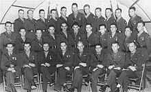 A large group of men in military uniforms pose for a photograph