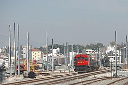 Work in progress at Acharnai Railway Center, while MLW diesel locomotive A-453 hauls southbound freight train 54507 over the existing Athens-Inoi line, 2008-02-01.
