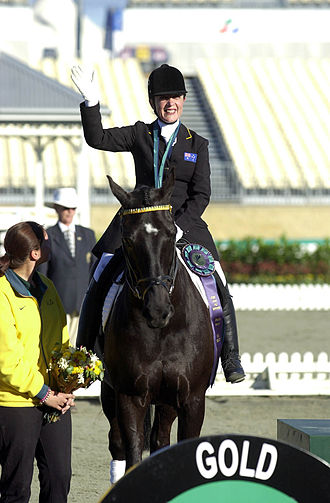 Equestrian at the 2000 Summer Paralympics - Higgins waves to the crowd from the gold medal podium. She won gold in the 2000 Summer Paralympics Individual Dressage Grade 3.