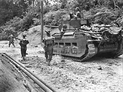 An armoured vehicle moves along a sandy road surrounded by jungle. Infantrymen advance alongside