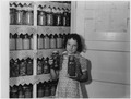 A girl holding two jars of canned goods - NARA - 196256.tif