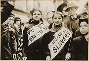 """Two girls wearing banners with slogan """"ABOLISH CHILD SLAVERY!!"""" in English and Yiddish. Probably taken during May 1, 1909 labor parade in New York City."""