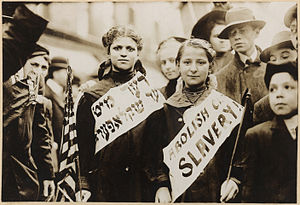 "History of the Jews in the United States - Half-length portrait of two girls wearing banners with slogan ""ABOLISH CHILD SLAVERY!!"" in English and Yiddish. Probably taken during May 1, 1909 labor parade in New York City."