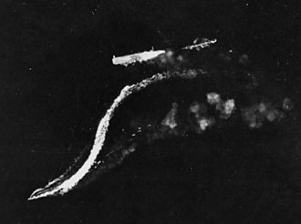 Battle of the Eastern Solomons - The disabled Ryujo (just right of center) under high-level attack by B-17 bombers on 24 August 1942. The destroyer Amatsukaze (center bottom) is moving away from Ryujo at full speed and Tokitsukaze (faintly visible, center right) is backing away from the bow of Ryūjō to evade the falling bombs.