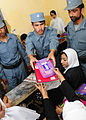 Afghan National Civil Order Police patrolmen hand out school supplies to students in a Kabul classroom. (4678254506).jpg