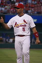 A man wearing a uniform that shows two cardinals sitting on a baseball bat