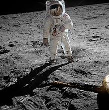 Aldrin in a space suit stands on the grey soil of the Moon. Armstrong and the Lunar module are reflected in his visor.