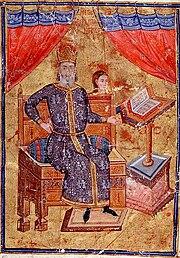 Vieil homme barbu assis sur un trône en bois, pointant vers un lutrin avec un livre ouvert dessus.  Il est vêtu d'un long caftan bleu brodé de blanc et bordé d'or, et porte un chapeau bombé doré-rouge.