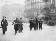 Black and white photo of men with guns on a street