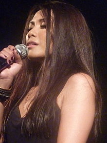A woman with long black hair holding a microphone while closing her eyes.