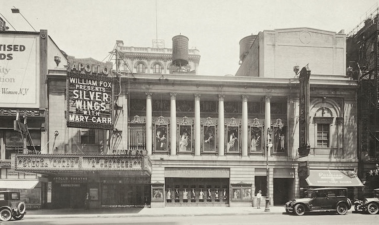 Theater building facade with colonnade spanning second and third stories and marquee and entrance on the left for two theaters.