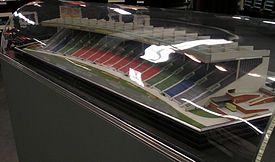 A scale model of stadium seating enclosed within a glass or plastic bubble which reflects an overhead light. There are nine columns of seats in the centre coloured red, two columns on each side of those coloured green, then one column on each side is blue, and one column on each side is grey. The seating is covered by an overhanging roof, and the structure has a concave arc shape.