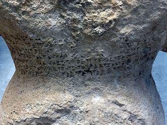 Assyrian statue (BM 124963) - Detail showing cuneiform inscription on rear waist of statue.