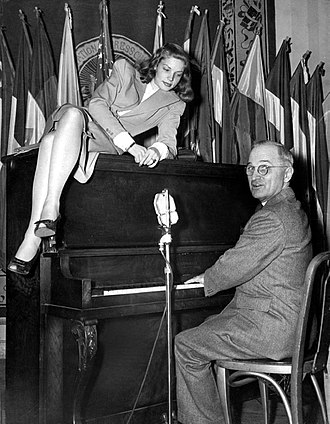 Lauren Bacall - Bacall lounges on top of the piano while Vice President Harry S. Truman plays for servicemen at the National Press Club Canteen in Washington, D.C. (February 10, 1945)