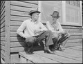 Blaine Sergent, left, talks with a fellow miner in the front porch of the company store on Saturday morning. Talking... - NARA - 541317.tif