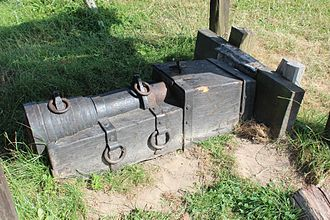 Gun carriage - A medieval bombard on a wooden bed staked to the ground.