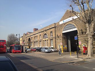 "East London (bus company) - The front facade of Bow Garage, showing the two great arches which are used on an ""in"" and ""out"" basis for access"