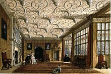A large room with an elaborate textured ceiling. The walls are oak-panelled, and there are a number of Davenport family portraits. There is a fireplace on the left, and two large bay windows on the right. There is a chair in the closest window, and there are a few people in the room.