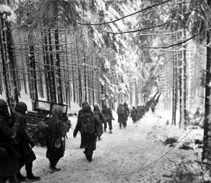 289th Infantry Regiment (United States) - Soldiers of the 289th Infantry march along the snow-covered road on their way to cut off the Saint Vith-Houffalize road in Belgium on 24 January 1945