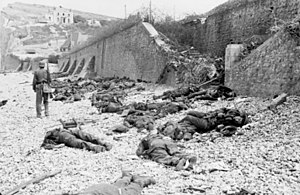 "Enfilade and defilade - The deadly result of enfilade fire during the Dieppe Raid of 1942: dead Canadian soldiers lie where they fell on ""Blue Beach"". Trapped between the beach and fortified sea wall, they made easy targets for MG 34 machineguns in a German bunker. The bunker firing slit is visible in the distance, just above the German soldier's head"