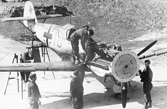 Synchronization gear - The synchronization gear of a Messerschmitt Bf 109E is adjusted (January 1941). A wooden disk attached to the propeller is used to indicate where each round passes through the propeller arc.