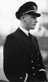 A black-and-white photograph of a man in semi profile wearing a dark military uniform and peaked cap.
