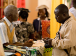 Buyers and artisans conduct business at a trade showcase supported by USAID West Africa Trade Hub (16637178273).png