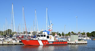 Gimli, Manitoba - The CCGS Vakta docked in the Gimli Harbour, with sailing vessels and the lighthouse in the background.
