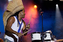 A side view of Carlinhos Brown performing drums.