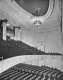 Interior of 1100-seat auditorium, showing main floor, balcony, and ceiling decoration and lamps
