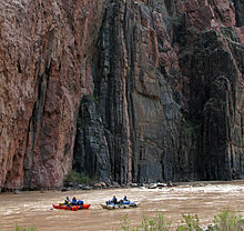 View of two small boats in a river, with high cliffs rising immediately behind them