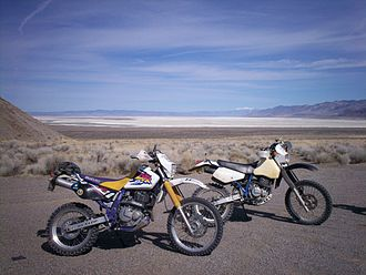 Dual-sport motorcycle - The Suzuki DR650 on the left and 1990 DR350 on the right are on a desert excursion including sandy roads, rocky two-tracks, dry lakes and rough single-tracks.